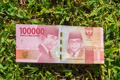 Hundred thousand rupiah paper money on green grass. Hundred thousand Indonesia rupiah paper money on a green grass Stock Image