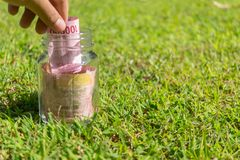 Rupiah Paper Money in jar on Green Nature Background. Hundred Thousand Rupiah Paper Money in jar on Green Nature Background with holding the money Royalty Free Stock Image