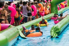 Hundreds Of People Take Part In Huge Atlanta Waterslide Event. Atlanta, GA, USA - July 15, 2017:  People carrying innertubes stand in a long line waiting their Royalty Free Stock Images