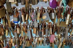 Many padlocks fixed to a bridge as tokens of love. Hundreds of small padlocks fixed to a bridge over a river as tokens of love Royalty Free Stock Photo