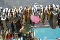 Many padlocks fixed to a bridge as tokens of love. Hundreds of small padlocks fixed to a bridge over a river as tokens of love Stock Photo