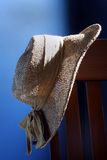 Hung Hat. A straw hat hangs on a chair with blue background royalty free stock image