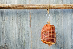 Hung Smoked Boneless Ham Hock Wrapped in Netting. Smoked boneless pork ham hock wrapped in netting hanging on a hook from a wooden pole with a weathered wood Royalty Free Stock Images