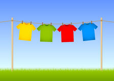 Hung T-shirts. On washing line with grass and blue sky in the background Stock Image