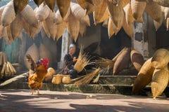 Hung Yen,越南- 2016年7月9日:有许多竹鱼陷井、公鸡和做传统bambo的女性工匠的老房子围场 免版税库存图片