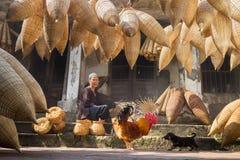 Hung Yen,越南- 2016年7月9日:有许多竹鱼陷井、公鸡和做传统bambo的女性工匠的老房子围场 库存照片