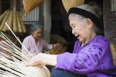 Hung Yen, Vietnam - 26. Juli 2015: Alte Frau spinnt Bambusfischfalle am vietnamesischen traditionellen Handwerksdorf Thu Sy, Pro  Stockfotografie