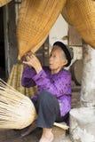 Hung Yen, Vietnam - 26. Juli 2015: Alte Frau spinnt Bambusfischfalle am vietnamesischen traditionellen Handwerksdorf Thu Sy, Pro  Stockbild