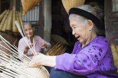 Hung Yen, Vietnam - 26. Juli 2015: Alte Frau spinnt Bambusfischfalle am vietnamesischen traditionellen Handwerksdorf Thu Sy, Pro  Stockbilder