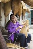 Hung Yen, Vietnam - 26. Juli 2015: Alte Frau spinnt Bambusfischfalle am vietnamesischen traditionellen Handwerksdorf Thu Sy, Pro  Lizenzfreie Stockfotografie