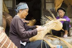 Hung Yen, Vietnam - 26. Juli 2015: Alte Frauen spinnt Bambusfischfalle am vietnamesischen traditionellen Handwerksdorf Thu Sy, Pr Lizenzfreie Stockbilder