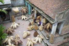 Hung Yen, Vietnam - 26. Juli 2015: Altes Haus im Land mit alten Frauen spinnt Bambusfischfalle am vietnamesischen traditionellen  Lizenzfreie Stockfotografie
