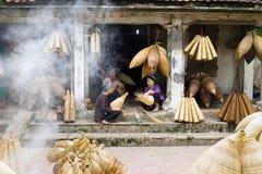 Hung Yen Vietnam - Juli 26, 2015: För vävbambu för gamla kvinnor fälla för fisk på den vietnamesiska traditionella hantverkbyn Th Royaltyfria Bilder