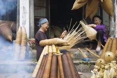 Hung Yen Vietnam - Juli 26, 2015: För vävbambu för gamla kvinnor fälla för fisk på den vietnamesiska traditionella hantverkbyn Th Royaltyfri Foto