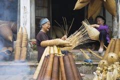 Hung Yen Vietnam - Juli 26, 2015: För vävbambu för gamla kvinnor fälla för fisk på den vietnamesiska traditionella hantverkbyn Th Arkivfoto