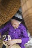 Hung Yen Vietnam - Juli 26, 2015: För vävbambu för gammal kvinna fälla för fisk på den vietnamesiska traditionella hantverkbyn Th Royaltyfria Bilder