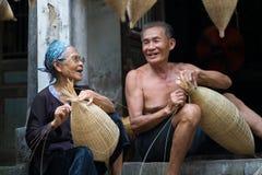 Hung Yen Vietnam - Juli 9, 2016: Parhantverkare som gör traditionell bambu att fiska fälla på hennes gamla hus i Thu Sy handelby royaltyfri bild