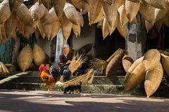 Hung Yen, Vietnam - July 9, 2016: Old house yard with many bamboo fish trap, a cock, and female craftsman making traditional bambo. O fish trap at her old house Royalty Free Stock Photos