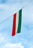Hungarian flag. Waving in the wind, with blue sky and white cirruses in the background royalty free stock images