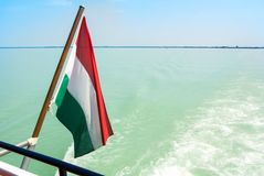 Hungarian flag at the cruise ship with bright light blue water o. F Balaton lake at the background Hungary Stock Images