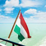 Hungarian flag flying fluttering waving in the wind at the forag. E of a cruise ship with beautiful dramatic cloudy sky and bright light blue water of Balaton Stock Image
