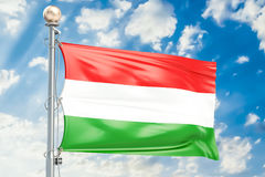 Hungarian flag waving in blue cloudy sky, 3D rendering Stock Image