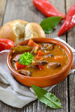Hungarian goulash soup. Hot Hungarian goulash soup served in a ceramic bowl with a fresh roll Royalty Free Stock Images