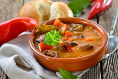 Hungarian goulash soup. Hot Hungarian goulash soup served in a ceramic bowl with a fresh roll Stock Photos
