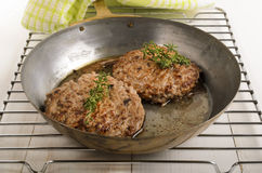 Hungarian mangalica burger with thyme in a brass pan Royalty Free Stock Photos