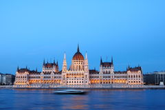 Hungarian Parliament Building. Illuminated at dusk, along Danube River, with a ship traveling on the river Royalty Free Stock Images