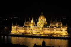 Hungarian Parliament Building at Night. A view across the Danube River of The Hungarian Parliament Building lit bright yellow at night.  It is also known as the Royalty Free Stock Images