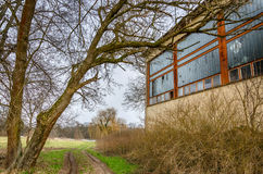 Hungarian rural decay - abandoned building, tree and dirt road to the Tisza (Tisa) river Royalty Free Stock Photography