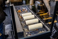 Hungarian tradition spit cake - Kurtoskalacs. Baking the Hungarian tradition spit cake - Kurtoskalacs at a christmas market at Vorosmarty Ter in Budapest stock photo