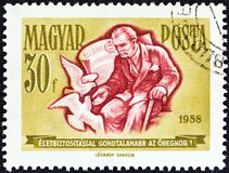 HUNGARY - CIRCA 1958: A stamp printed in Hungary from the `Savings Campaign` issue shows old man feeding pigeons, circa 1958.