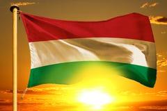 Hungary flag weaving on the beautiful orange sunset with clouds background. Hungary flag weaving on the beautiful orange sunset background stock photo