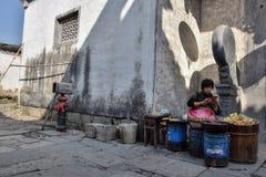 "HUNGCUN村庄,安徽,中国†""大约2017年10月:在金属桶后的一妇女选址 库存图片"