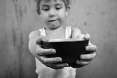 Hunger. A close-up  of a boy holding an empty bowl Stock Photo