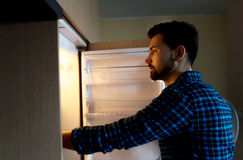 Hunger, food and fridge. Young man is looking for some food in fridge royalty free stock image