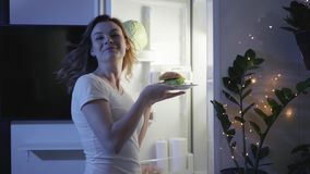 Hunger at night, hungry smiling woman walks to fridge chooses a hamburger that is not healthy and shows her finger