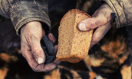 Hunger and poverty. A loaf of bread in an old mans hands Royalty Free Stock Photography