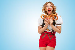 Hunger for pretzels. Young sexy Swiss woman wearing red jumper shorts with suspenders in a form of a traditional dirndl, holding with hunger two pretzels on Royalty Free Stock Photography