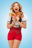 Hunger for pretzels. Young sexy Swiss woman wearing red jumper shorts with suspenders in a form of a traditional dirndl, holding with hunger two pretzels on Royalty Free Stock Image