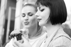 Hunger, temptation, appetite concept. Women look at cupcake in paris, france. Girl friends with blueberry muffin in cafe. Dessert, food snack pastry Royalty Free Stock Photos