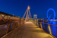 Hungerford Bridge and London Eye during blue hour. An empty Hungerford Bridge during the evening blue hour Royalty Free Stock Images