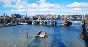 Hungerford Bridge on the Thames. Hungerford Bridge and boats on the London River Thames Royalty Free Stock Image