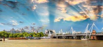 Hungerford bro på solnedgången med stadshorisont längs Themsen, Lond Royaltyfria Foton