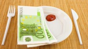 Hungern för pengar, 100 euroservetter, ketchup, plast- gaffel och kniv Royaltyfri Bild