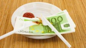 Hungern för pengar, 100 euroservetter, ketchup, plast- gaffel och kniv Royaltyfria Foton