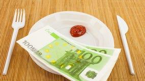 Hungern för pengar, 100 euroservetter, ketchup, plast- gaffel och kniv Fotografering för Bildbyråer