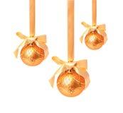 Hunging guld- julbollar som isoleras på en vit Arkivfoto